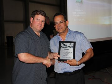 RJ Gomez, right, accepts 'Service Center of the Year Silver Award' from Matt Isley, Twin Commander President